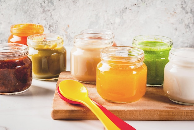 Variety of homemade baby vegetable and fruit puree,  white marble  copyspace