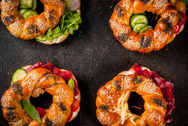 Variety of homemade bagels sandwiches with cream cheese,  ham, vegetables