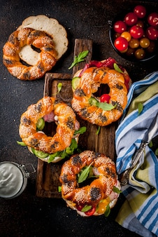 Variety of homemade bagels sandwiches with sesame and poppy seeds, cream cheese,  ham, radish, arugula, cherry tomatoes, cucumbers, on cutting board. dark concrete surface  top view