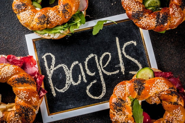 Variety of homemade bagels sandwiches with sesame and poppy seeds, cream cheese,  ham, radish, arugula, cherry tomatoes, cucumbers, dark concrete surface  above