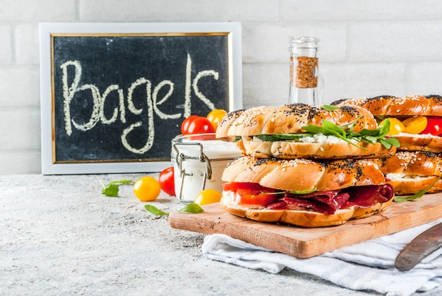 Variety of homemade bagels sandwiches with sesame and poppy seeds, cream cheese,  ham, radish, arugula, cherry tomatoes, cucumbers, white grey textured surface