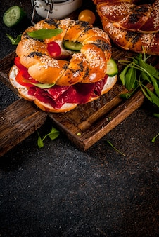 Variety of homemade bagels sandwiches with sesame and poppy seeds, cream cheese,  ham, radish, arugula, cherry tomatoes, cucumbers, with ingredients on dark concrete surface