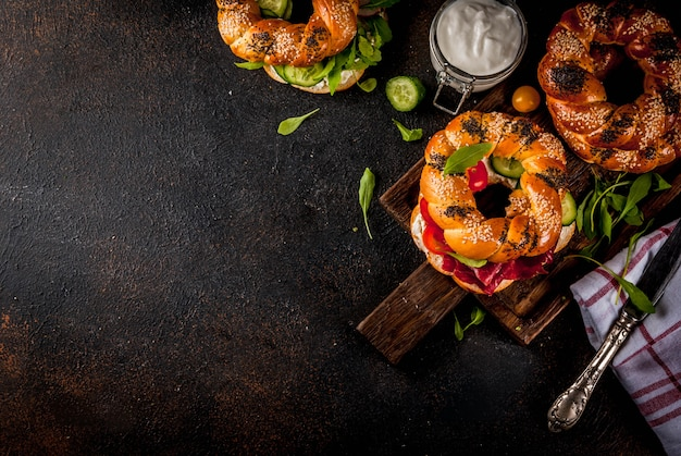 Variety of homemade bagels sandwiches with sesame and poppy seeds, cream cheese,  ham, radish, arugula, cherry tomatoes, cucumbers, with ingredients on dark concrete surface  above