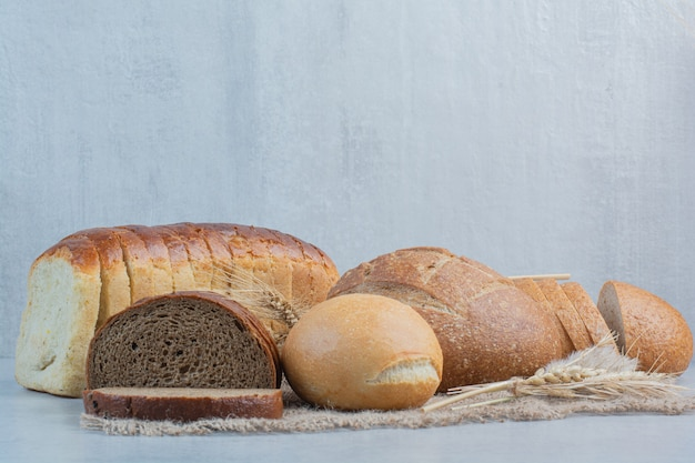 Variety of homemade bread on burlap with wheat. high quality photo