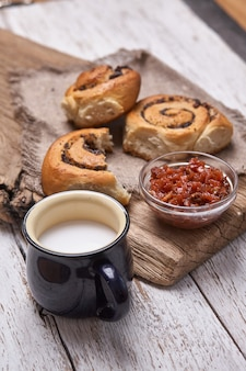 Variety of homemade puff pastry buns cinnamon served with milk cup, jam, butter as breakfast over white plank wooden table. flat lay, space
