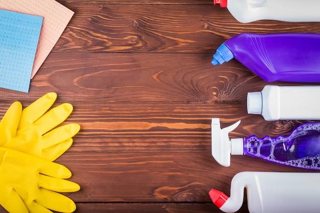 Разнообразие чистящих средств на деревянном столе с копией пространства, вид сверху