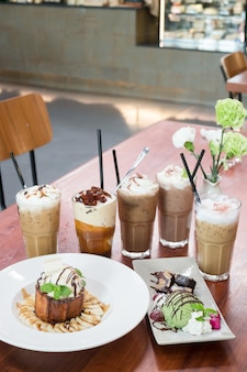 Variety iced coffee drinks on wooden table