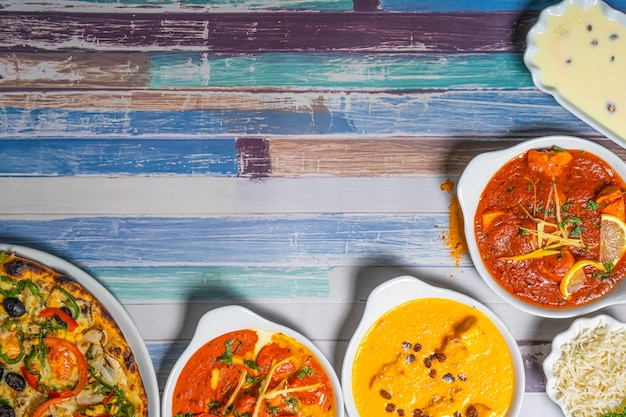 Variety of indian dishes on vintage wooden table. top view copy space