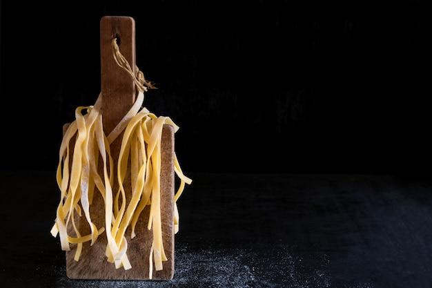 Variety of italian homemade raw uncooked pasta tagliatelle on black texture table.