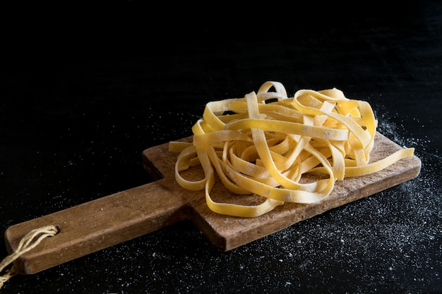A variety of italian homemade raw uncooked tagliatelle pasta on a cutting board