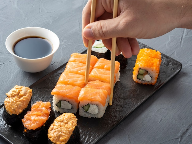 A variety of japanese rolls on a black plate with soy and a hand picking one up with chopsticks