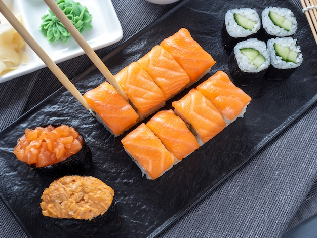 A variety of japanese rolls and sushi on a textured black plate. side view. bamboo chopsticks holding a single roll