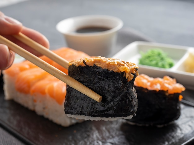 A variety of japanese rolls and sushi on a textured black plate. side view. bamboo sticks hold one gunkan. close up