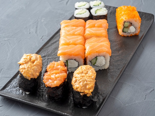 A variety of japanese rolls and sushi on a textured black plate. side view. close up. food composition