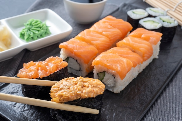 A variety of japanese rolls and sushi on a textured plate. side view. bamboo sticks of ginger and sauce nearby.