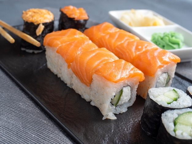A variety of japanese rolls and sushi on a textured plate side view