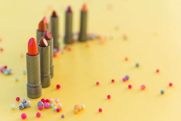 Variety of lipsticks shades arranged in row on yellow background