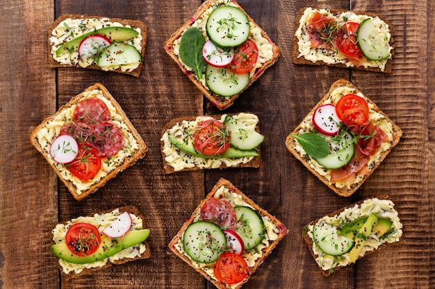Variety of mini sandwiches with cream cheese, vegetables and salami. sandwiches with cucumber, radish, tomatoes, salami on a gray background, top view. flat lay.