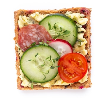Variety of mini sandwiches with cream cheese, vegetables and salami. sandwiches with cucumber, radish, tomatoes, salami on a white background, top view. flat lay.
