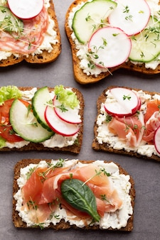 Variety of mini sandwiches with cream cheese, vegetables and salami.
