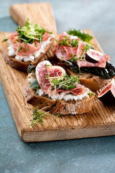 Variety of mini sandwiches with cream cheese vegetables and salami