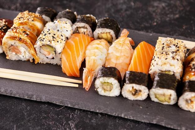 Разнообразие суши-роллов на черном фоне в студии фото