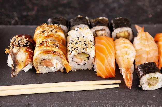 Mix di varietà di rotoli di sushi su sfondo nero in studio fotografico