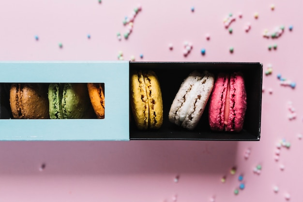 Variety of multicolored macaroons in gift box on pink background