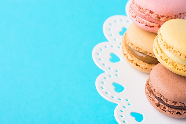 Variety of multicolored pink green yellow brown mocha coffee macarons stacked on cake stand on turquoise background