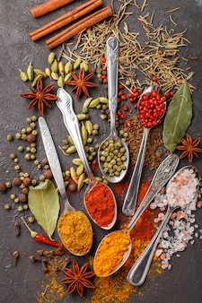 Variety of natural spices, seasonings and herbs in spoons on the stone table - paprika, coriander, cardamom, turmeric, rosemary, salt, pepper, cumin, chili, cinnamon, cloves, star anise