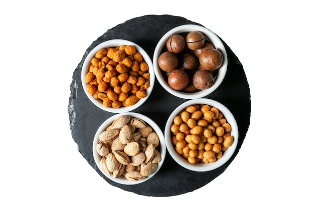 Variety of nuts in bowls on a stone board