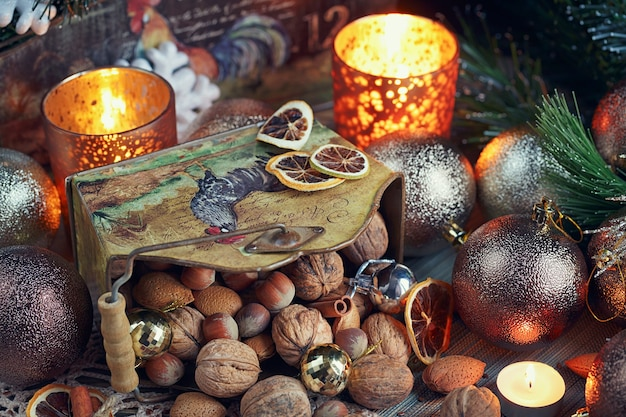 Variety of nuts in christmas and new year decoration. christmas and new year composition with fir tree branches, candles and holidays light on wooden background