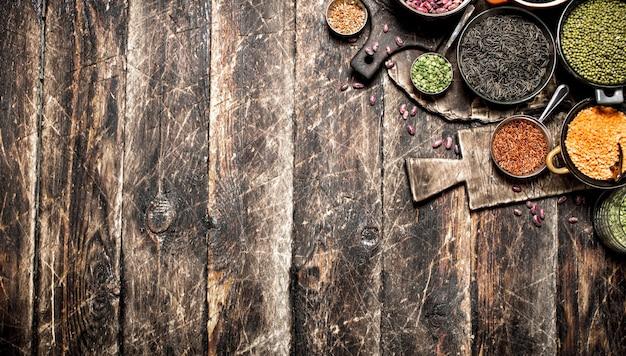 Разнообразие семян фасоли в миске на деревянном столе