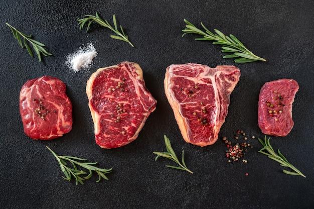 Разнообразие стейков из говядины на темной поверхности