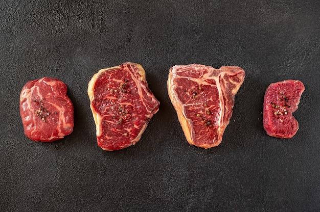 Разнообразие стейков из говядины на темном столе