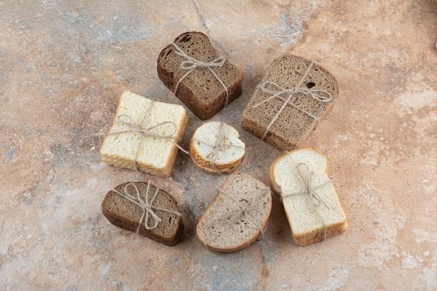 Разнообразие хлеба, перевязанного веревкой на мраморном фоне