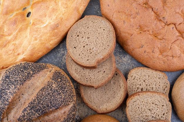 На мраморной поверхности собраны разные виды хлеба.