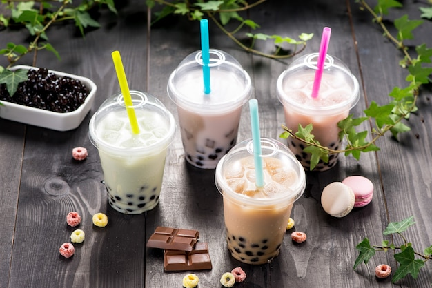 Разнообразие пузырькового чая в пластиковых стаканчиках с соломинкой на деревянном столе.