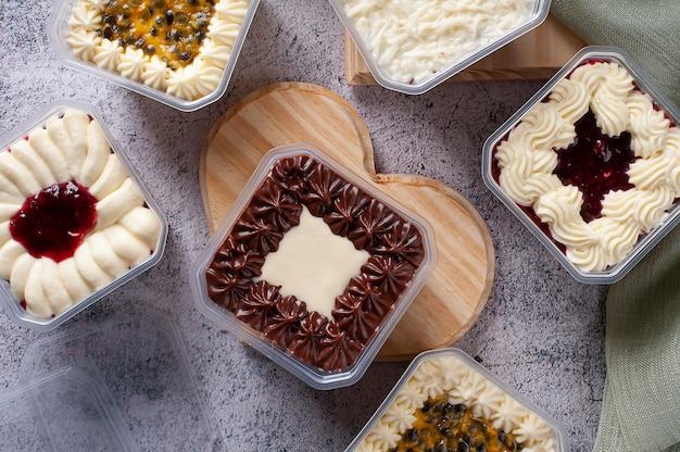 Разнообразие торта в горшочке для доставки. вкус клубники, маракуйи, шоколада и кокоса. вид сверху.
