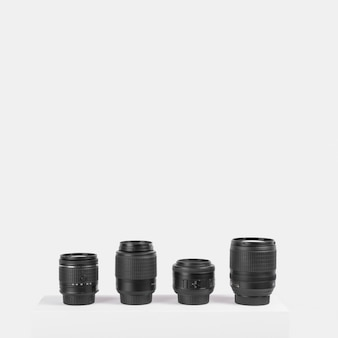 Variety of camera lenses arranged on table in front of white background