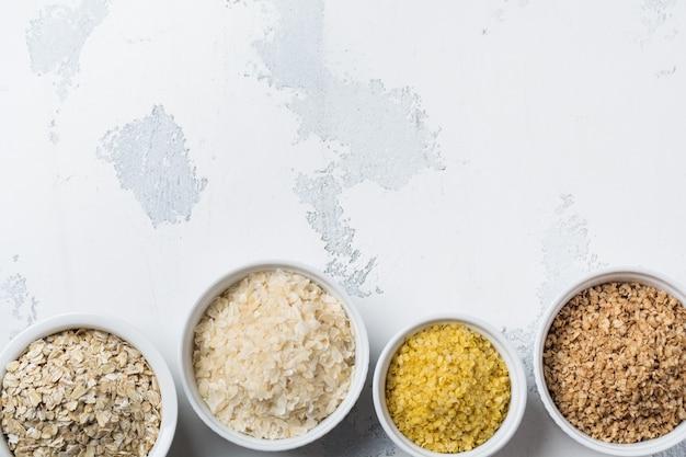 Сорта крупяные хлопья рисовые, пшенные, гречневые, овсяные. суперпродукты в белых керамических мисках деревянные
