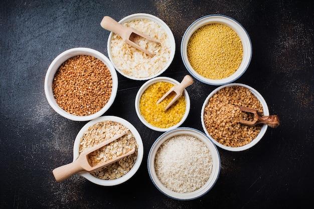 Сорта крупяные хлопья рисовые, пшенные, гречневые, овсяные. суперпродукты в белых керамических мисках