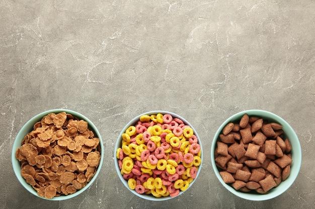 파란색 그릇에 담긴 다양한 시리얼, 회색 나무 배경에서 빠른 아침 식사. 세로 사진