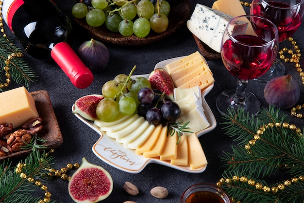 さまざまなチーズとフルーツがクリスマスツリーとしてプレートに添えられ、濃い灰色の背景にグラス2杯のワインが添えられています。大晦日パーティースナック