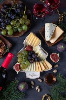 짙은 회색 배경에 와인 두 잔과 함께 다양한 치즈와 과일이 접시에 크리스마스 트리로 제공됩니다. 새해 전야 파티 스낵