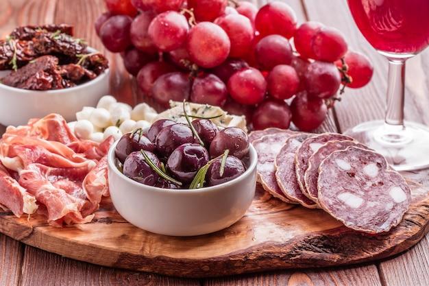 Разнообразие сыра и мяса на темной таблице.