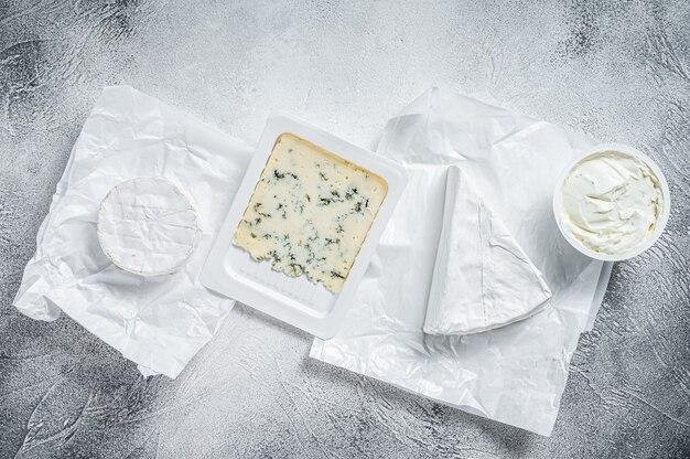Разнообразие сыров на кухонном столе, бри, камамбер, горгонзола и сливочный сыр с голубой плесенью. белый фон. вид сверху.