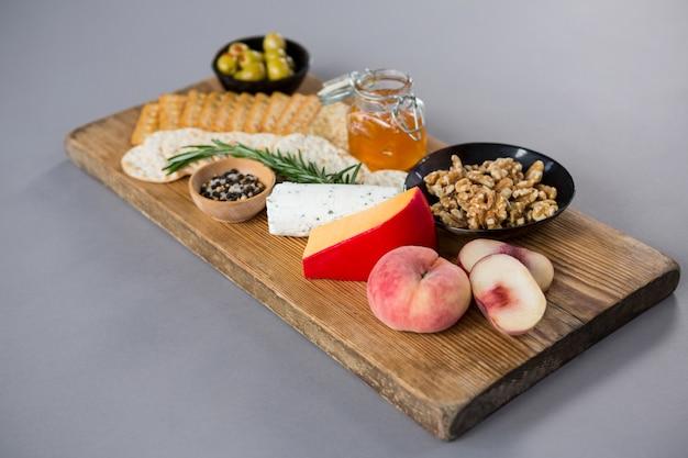 オリーブ、ピーチ、ハチミツ、ローズマリー、クルミ、クラッカー入りのチーズ各種