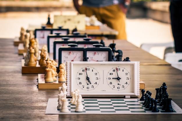 チェスのトーナメントのために、木製の机の上にピースと時計が付いたさまざまなチェスボード。最初の時計に選択的に焦点を当てます。アウトドアチェスの競争
