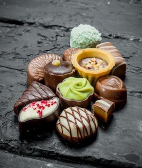 さまざまなチョコレート菓子。黒の素朴な背景に。